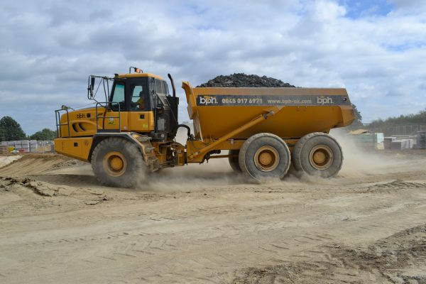 BPH-branded dumper truck on a construction site carrying aggregate