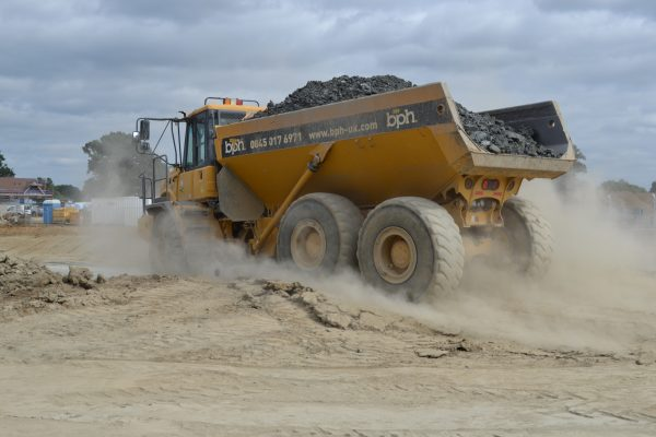 BPH dumper truck kicking up the dust as it drives off-site with a full load