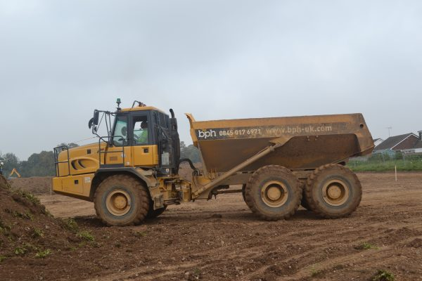 Side view of a BPH dumper truck being driven onto a construction site
