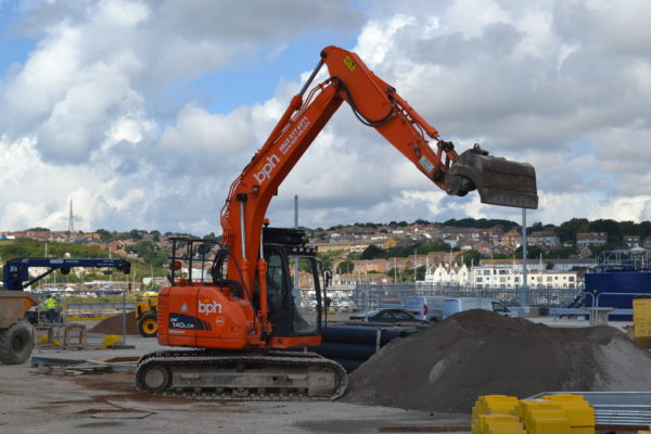 Doosan DX140W-3 wheeled excavator with its arm extended as it works on the seafront