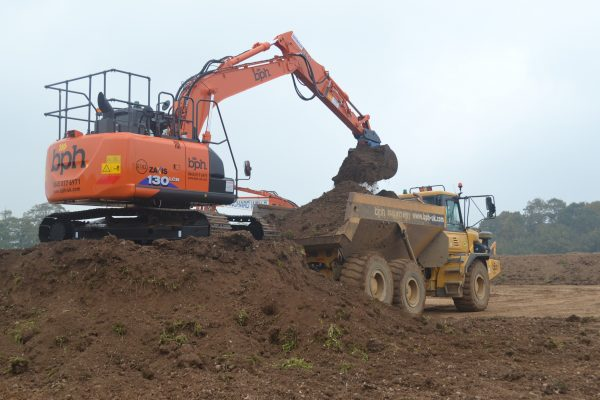 Hitachi ZX130-6 excavator pouring earth into a BPH branded dumper truck