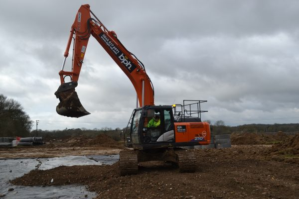 Hitachi ZX210-6 excavator being operated by a man on a muddy construction site