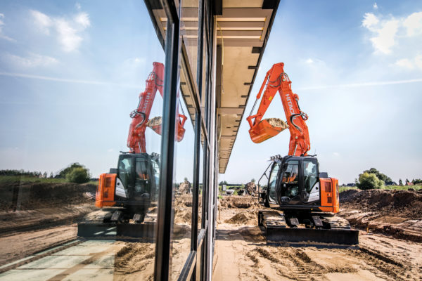 Hitachi ZX135US-6 mini excavator working alongside a building with reflective windows