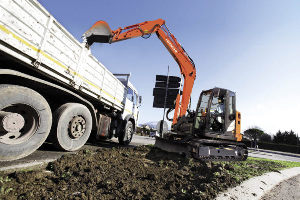 Man tipping earth from a mini excavator into a lorry