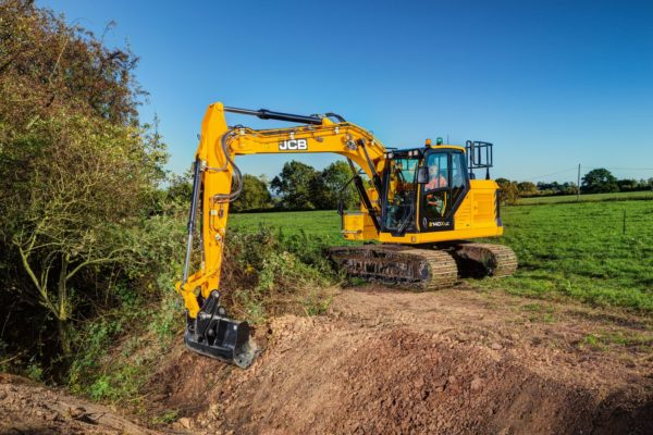 A yellow JCB 140X crawler excavator digging a trench in the ground next to a field