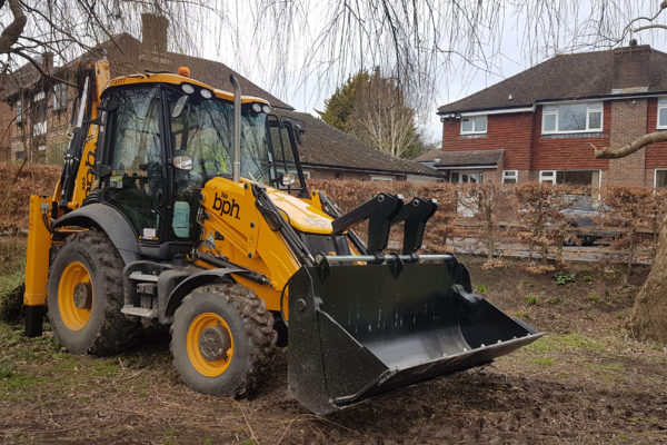 Yellow JCB industrial forklift parked on the grass in front of a house